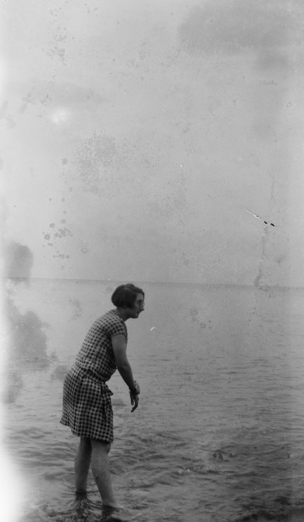 grayscale photography of woman standing near seashore