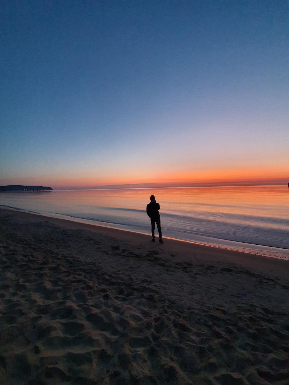 silhouette photo of man near beach