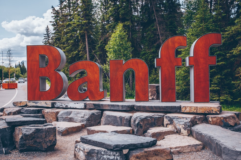 Banff freestanding letters on rocks beside road and trees