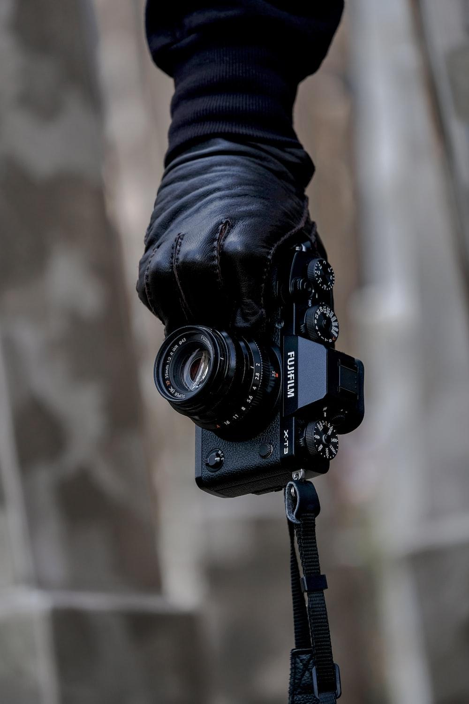 person's hand holding black Fujifilm bridge camera