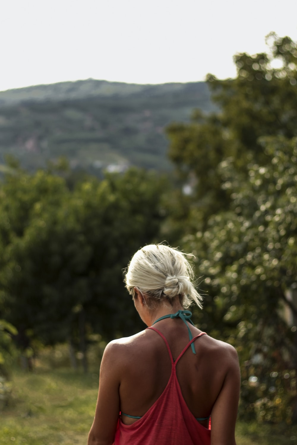 woman wearing pink tank top standing in front of green mountains