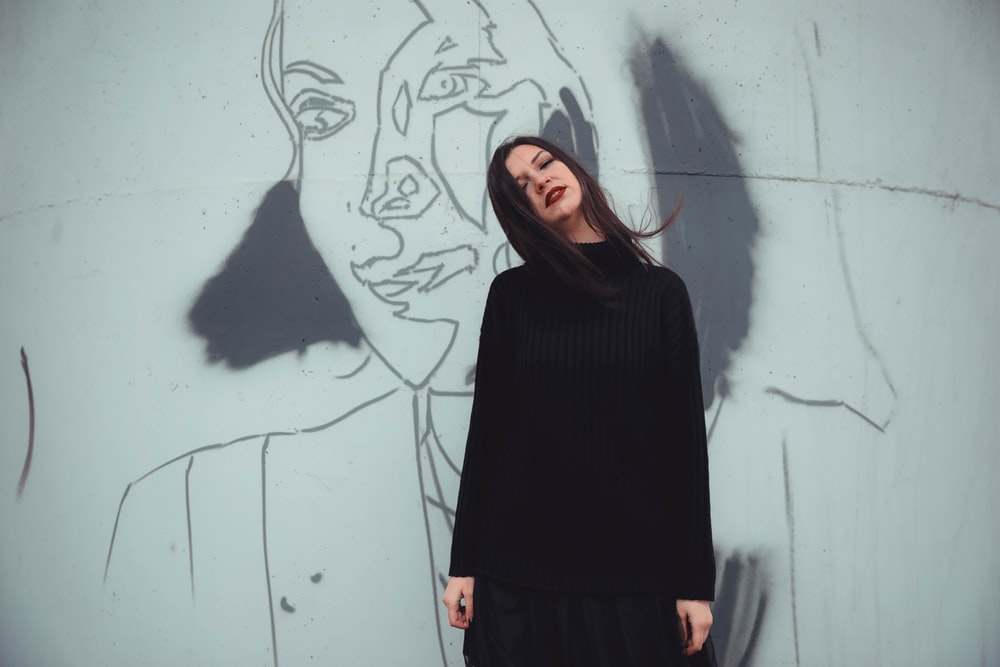 woman standing in front of wall with mural