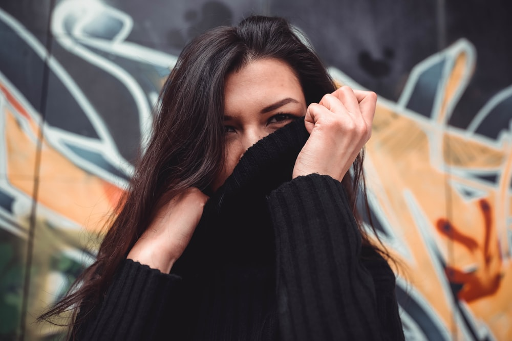 woman covering her face on black sweater