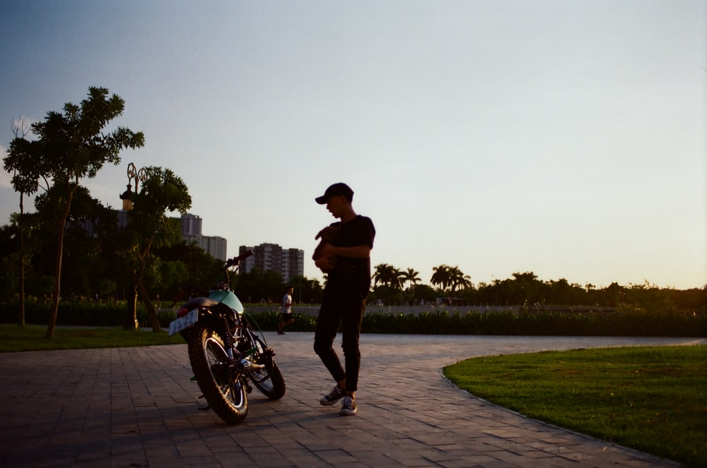 man standing beside motorcycle