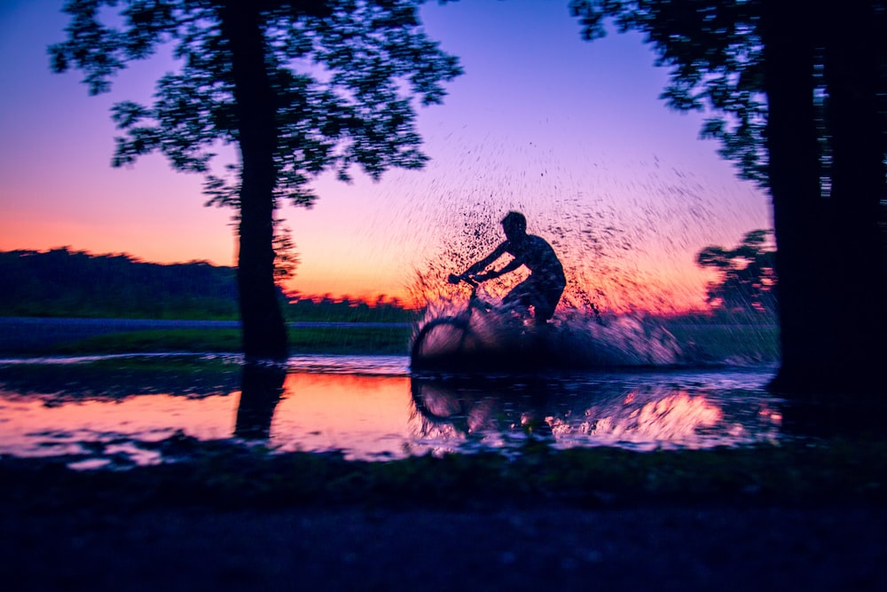 silhouette photo of man riding bicycle