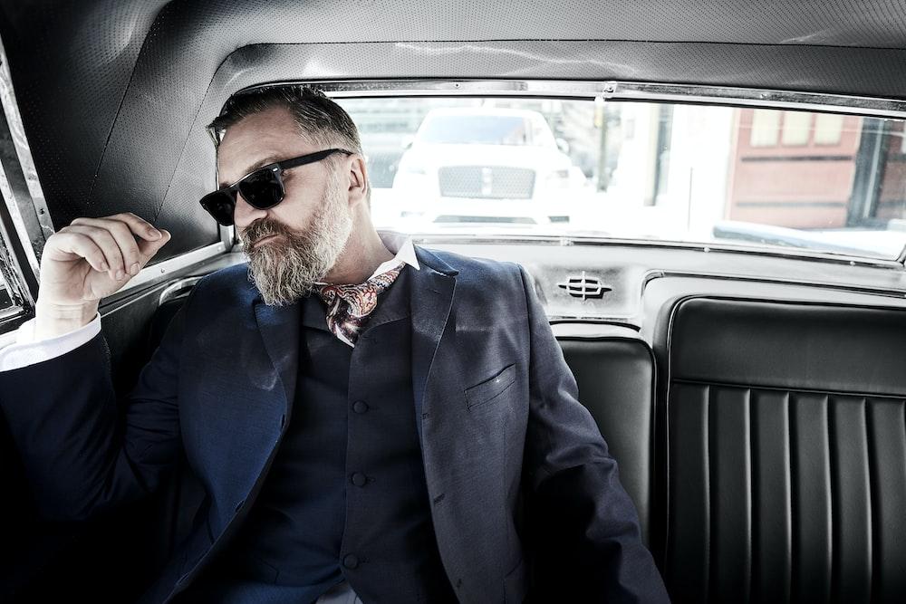 man wearing black sunglasses sitting inside vehicle