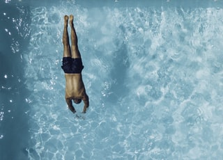 person about to dive on swimming pool