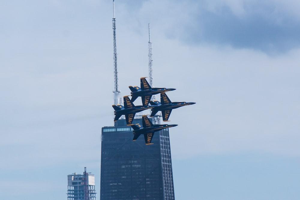 four airplanes in mid air near high-rise building