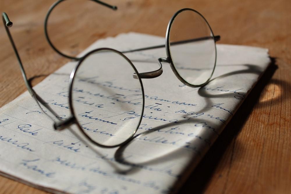 silver-colored framed eyeglasses on white printer paper