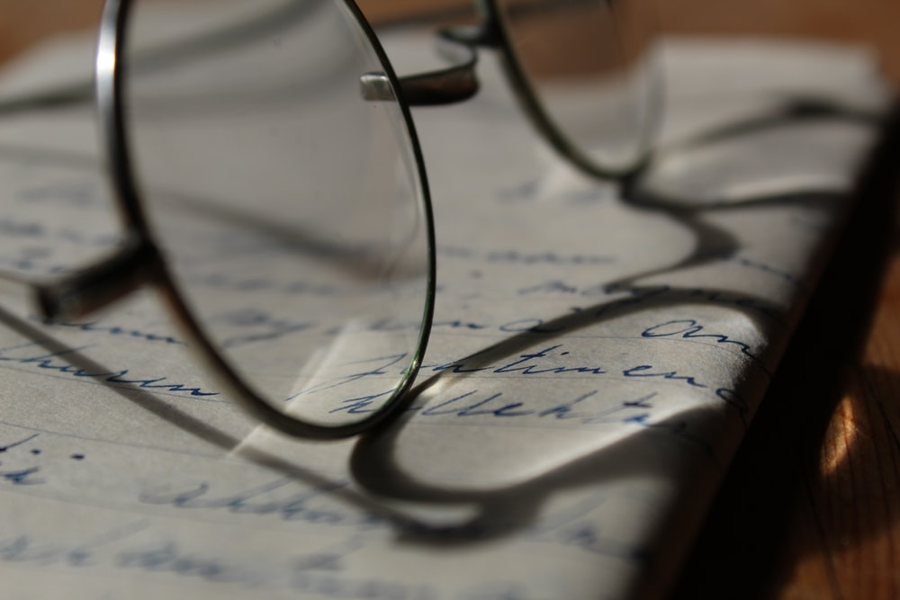 silver framed eyeglasses on paper with handwriting
