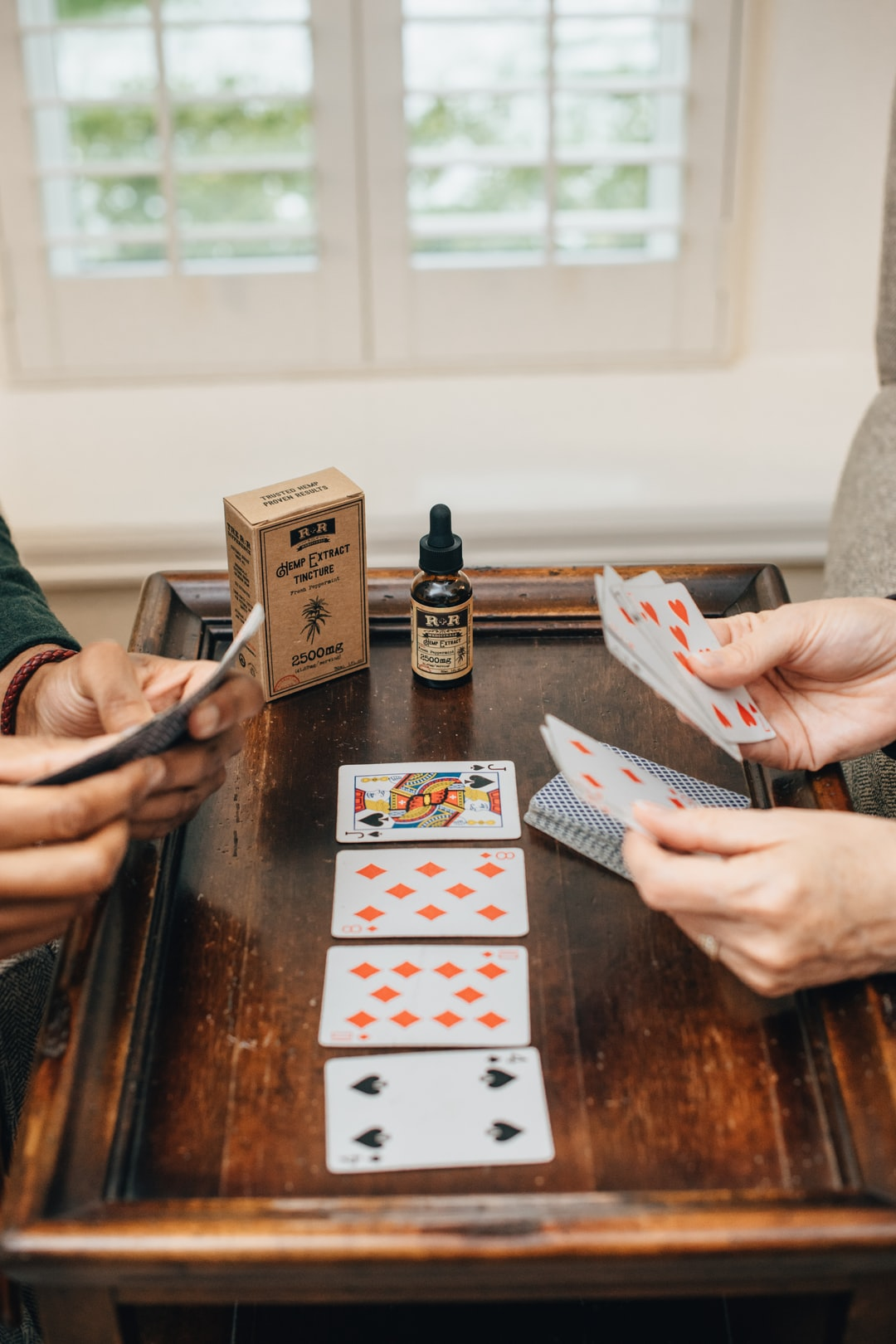 Colorado friends playing cards with hemp extract oil.