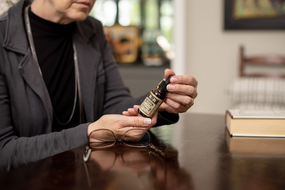 person holding brown bottle