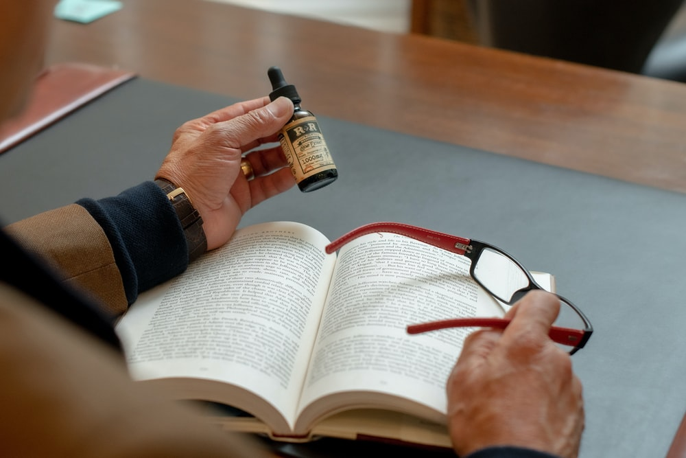 person holding small drop bottle and eyeglasses while reading book