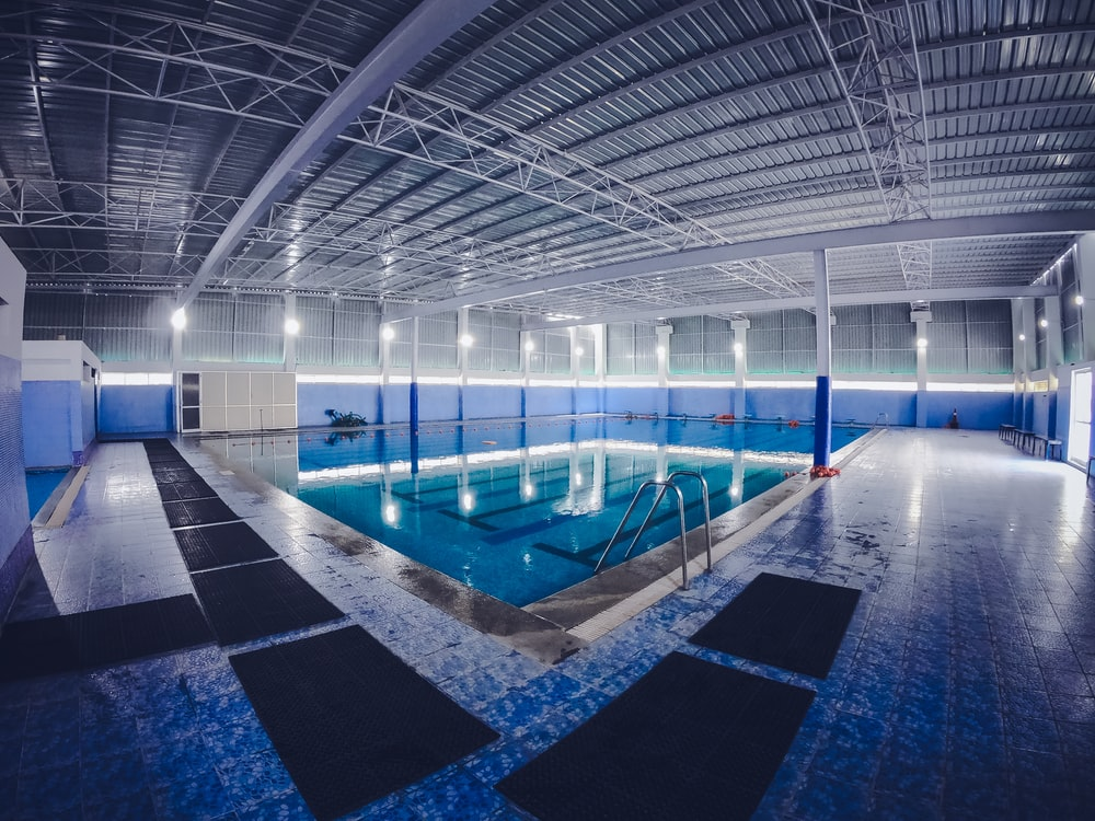 rectangular blue swimming pool inside building
