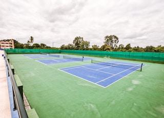 three blue lawn tennis courts