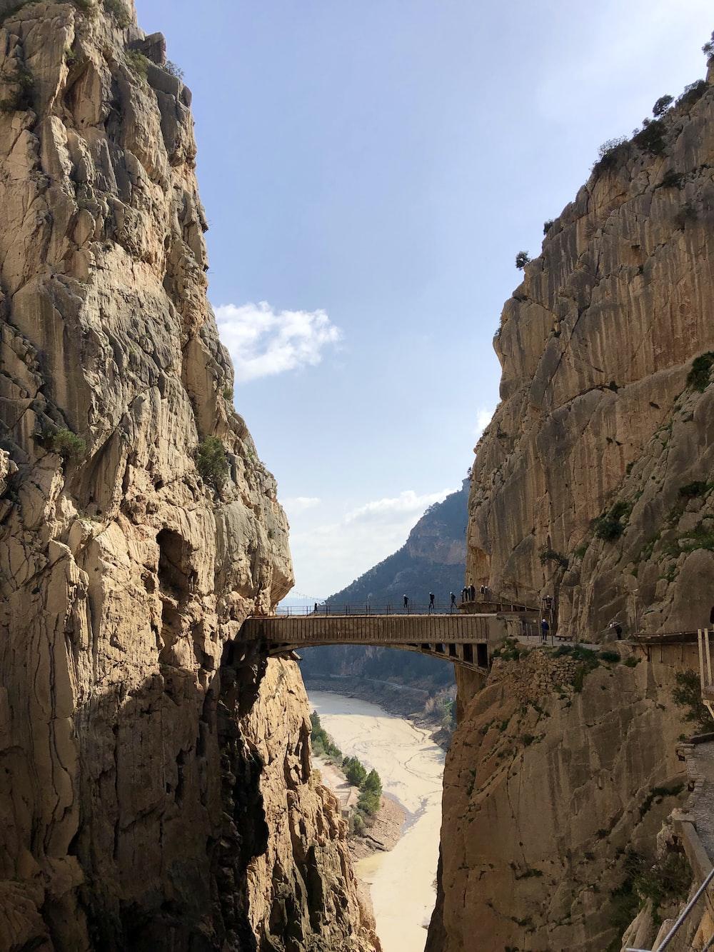 gray bridge between mountains during daytime