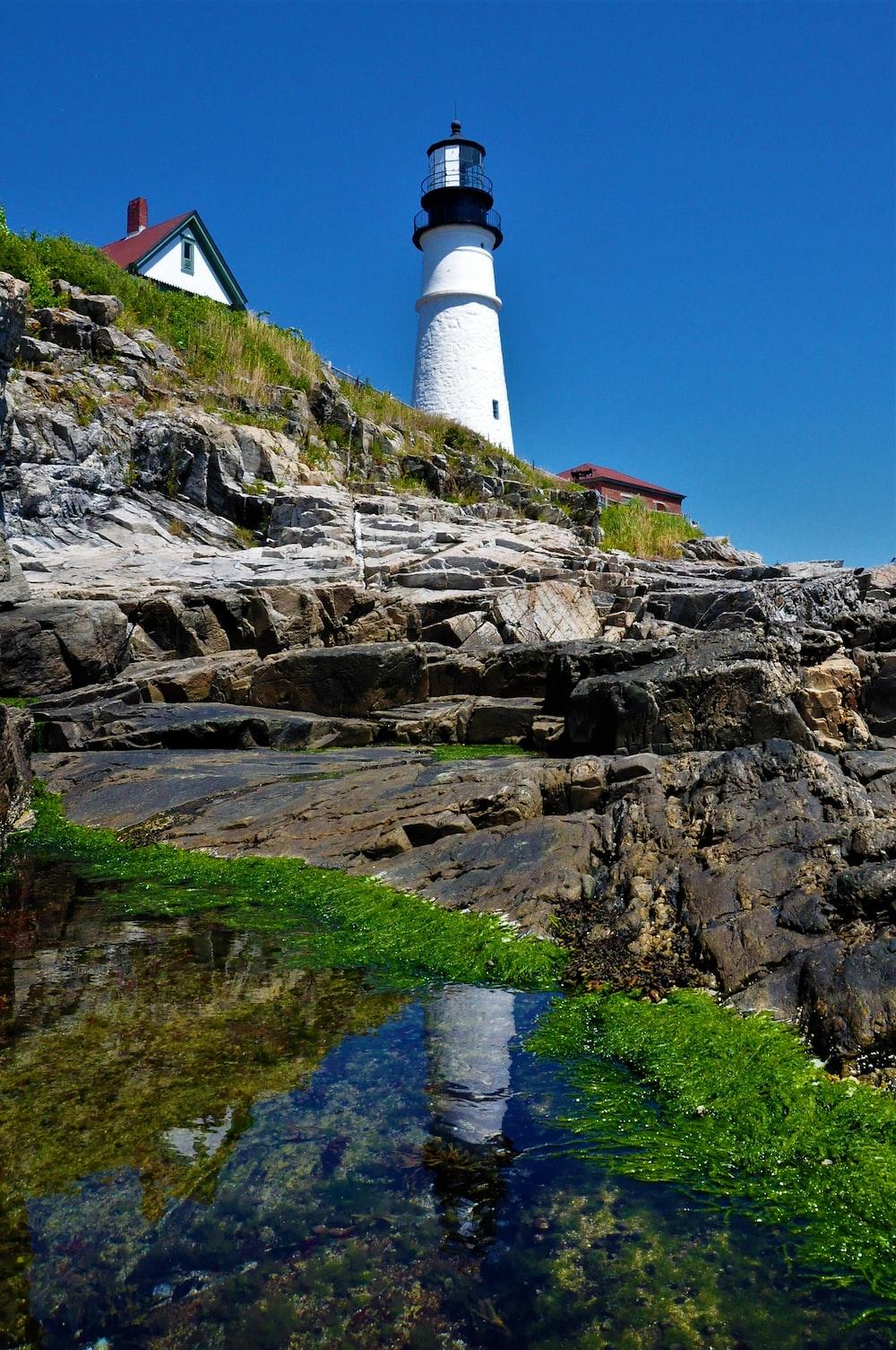 white concrete lighthouse near house