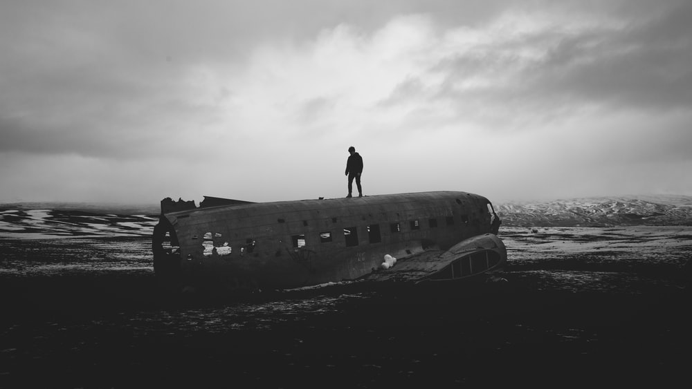 silhouette of man on top of wrecked airplane