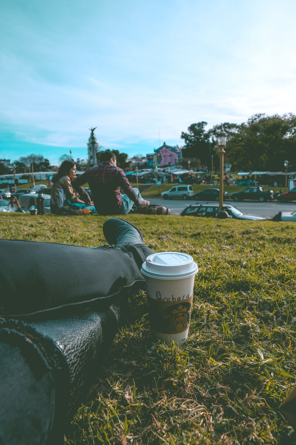 sitting person on grass beside white disposable cup
