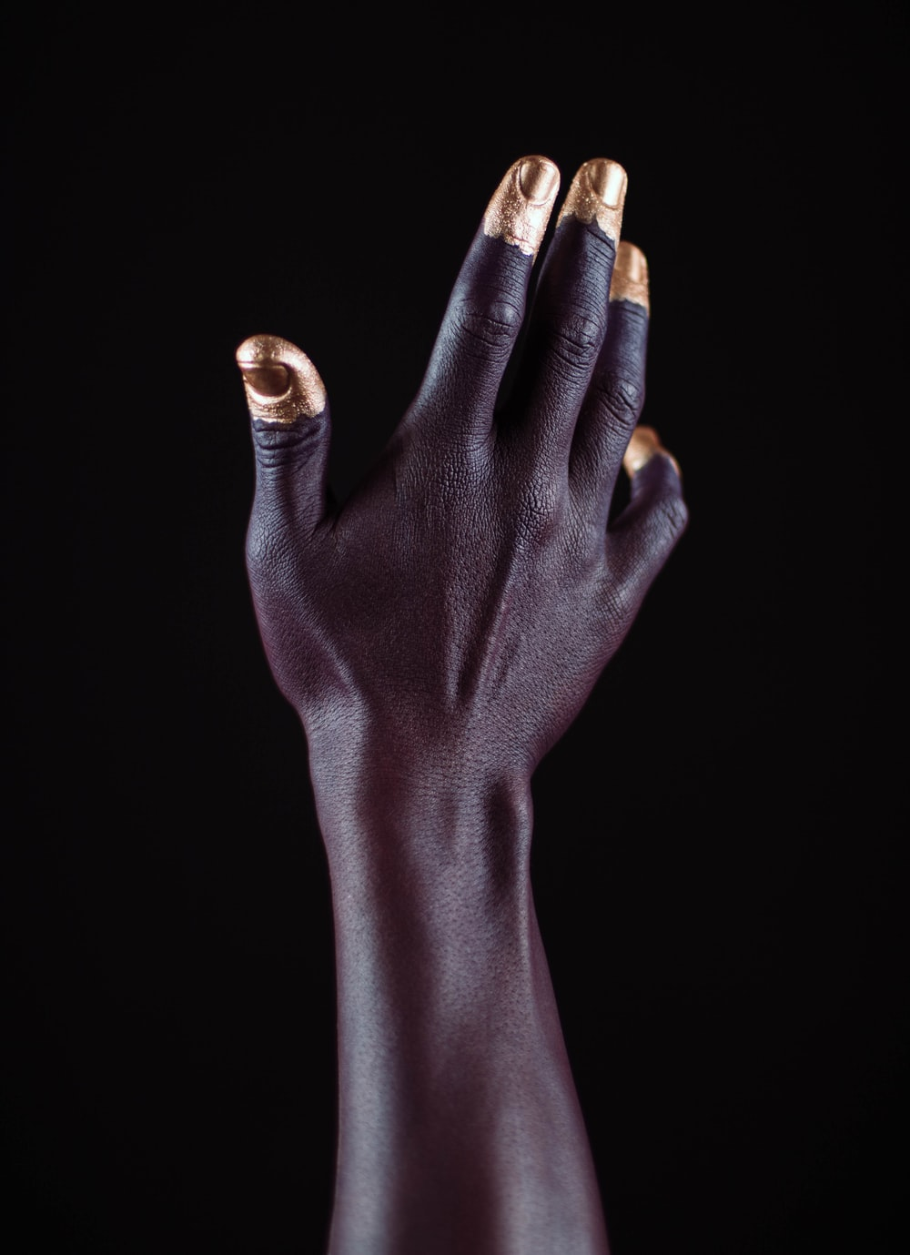 gold-dipped person's fingers