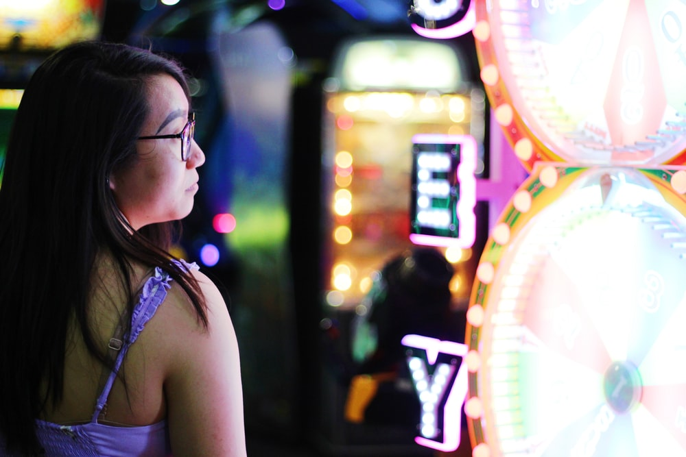 selective focus photography of woman standing beside lights