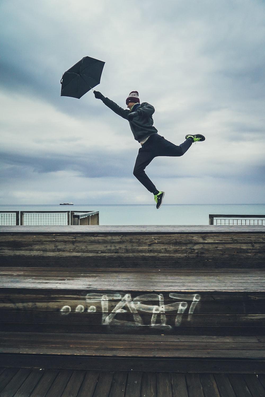 close-up photography of man jumping with umbrella