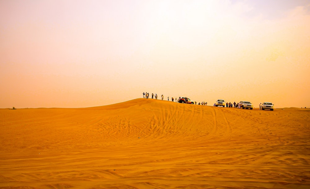 people and cars on desert during daytime