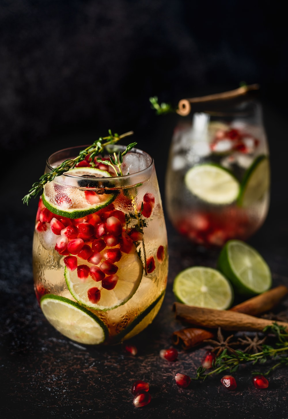 two glasses of cocktails with pomegranate and limes