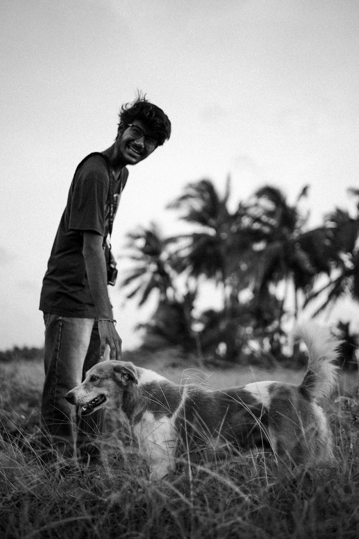 greyscale photography of man beside dog