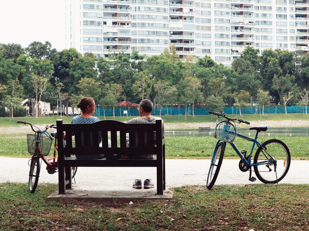 man and woman sitting on bench near two bikes viewing green field during daytime