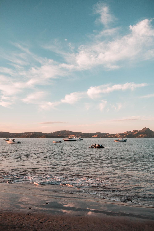 boats in sea under blue sky