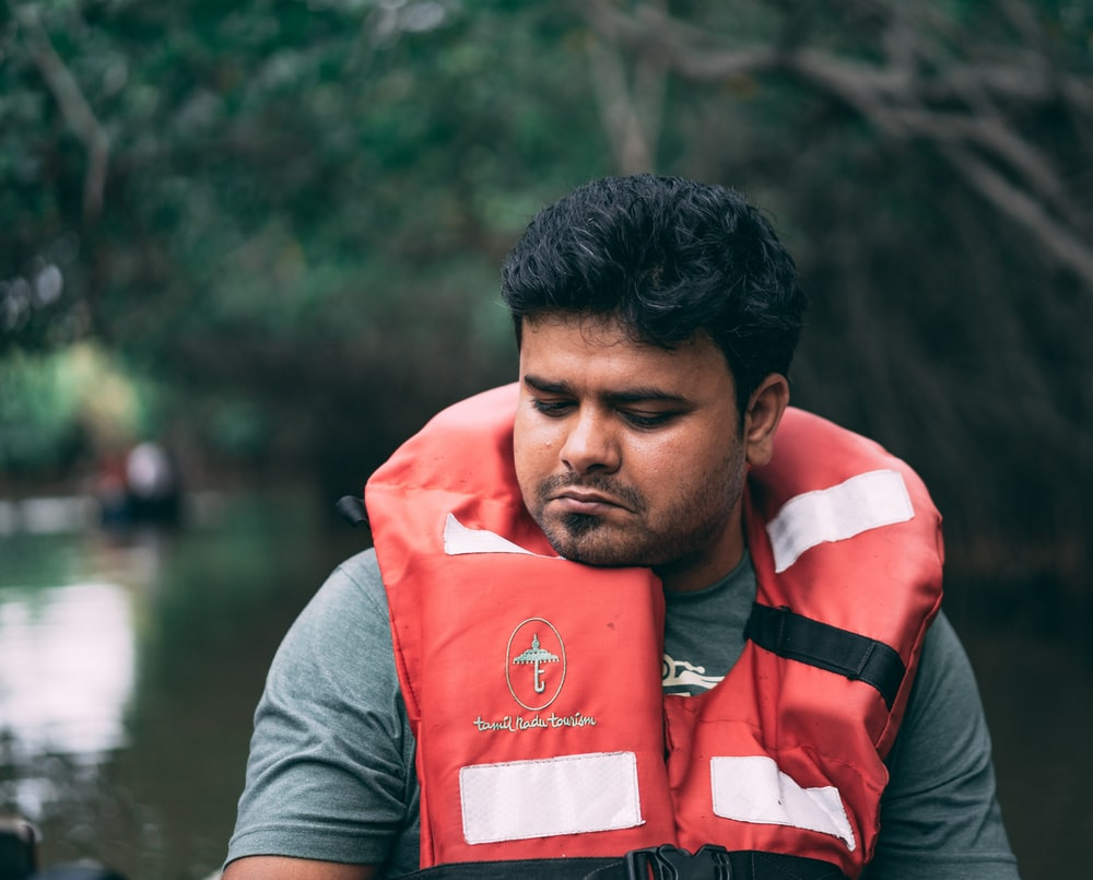 shallow focus photo of man wearing red lifevest
