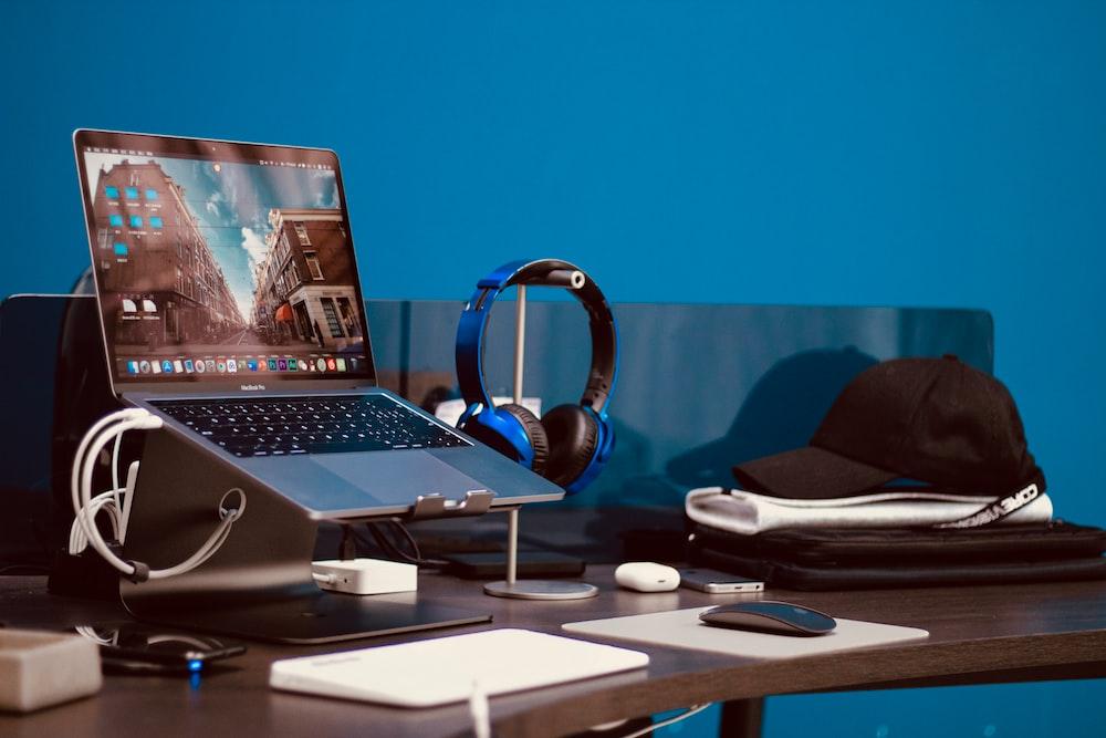 turned-on laptop beside headphones and cap on desk