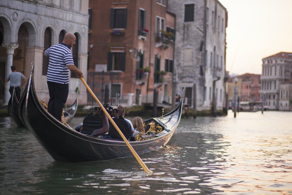 gondola boat sails with tourist at canal of Italy