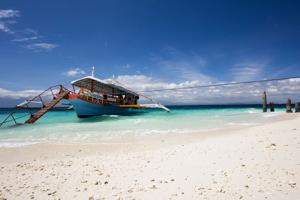 blue boat on seashore