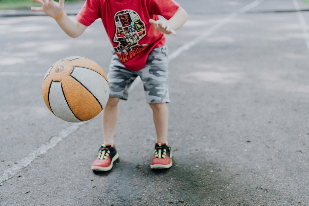 Little boy dribbling an orange and white basketball