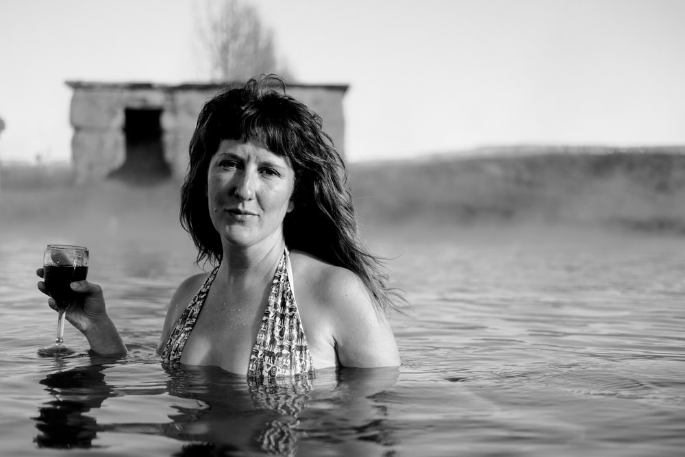 grayscale photography of woman underwater holding wine