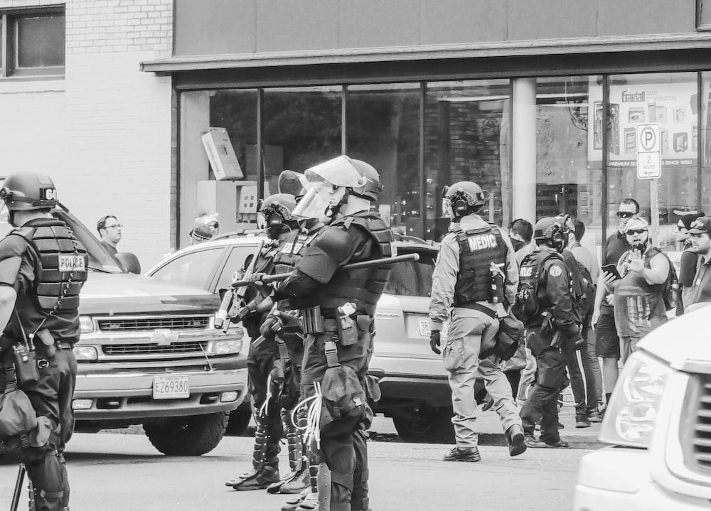 grayscale photo of policemen wearing gears