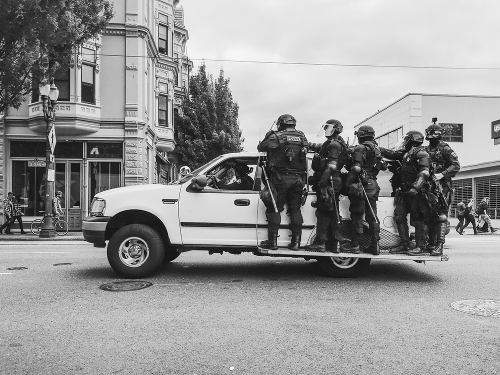 grayscale photo of men standing beside vehicle