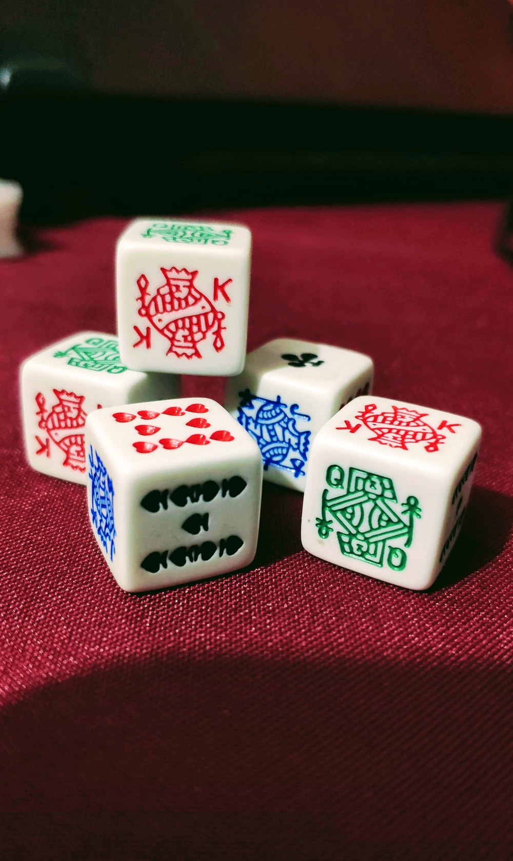 five playing dies on red cloth