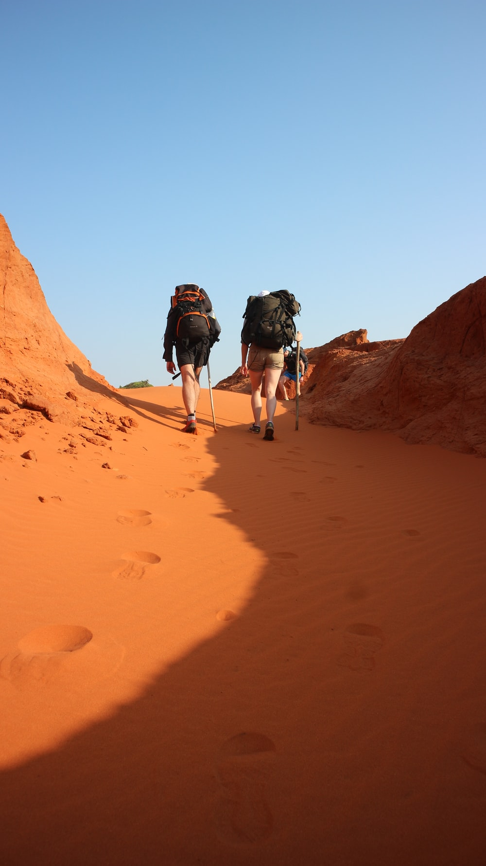 two person hiking on desert during daytime