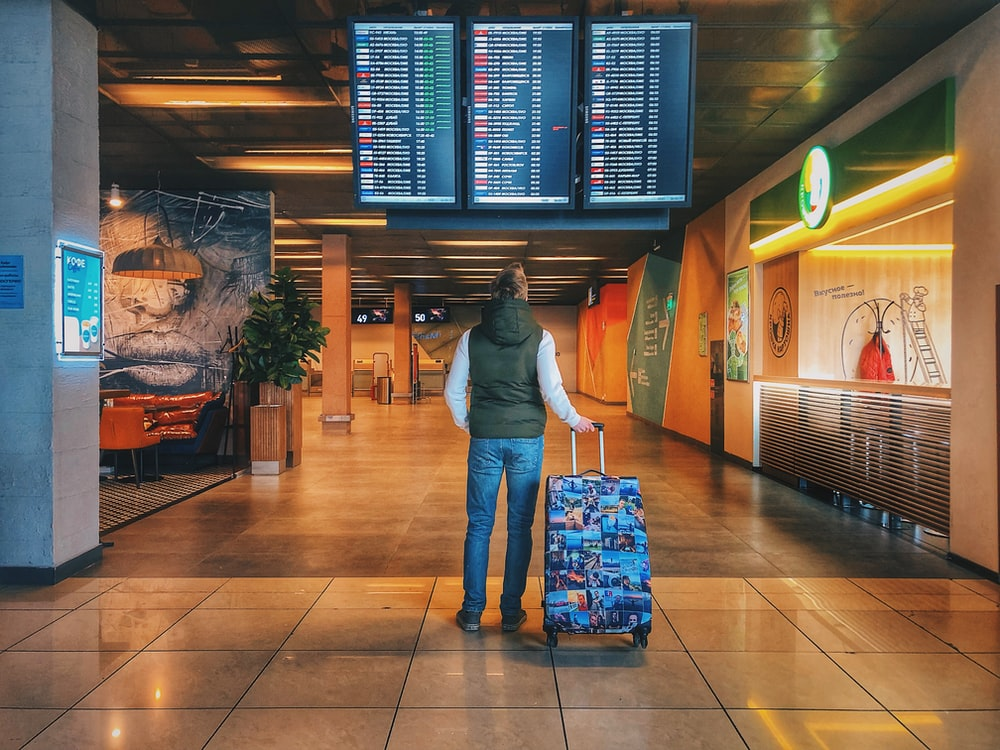 person standing with holding luggage bag