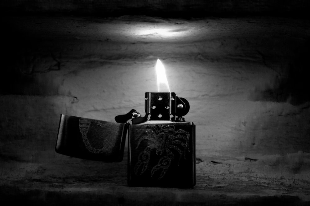grayscale photography of turned-on flip lighter