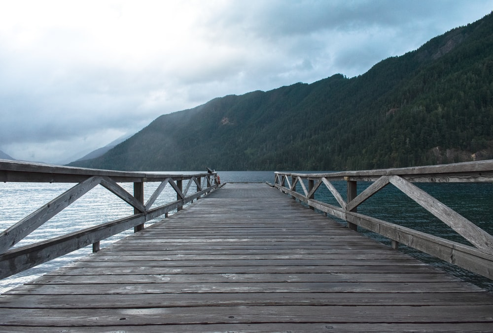 gray wooden dock near mountain during daytime