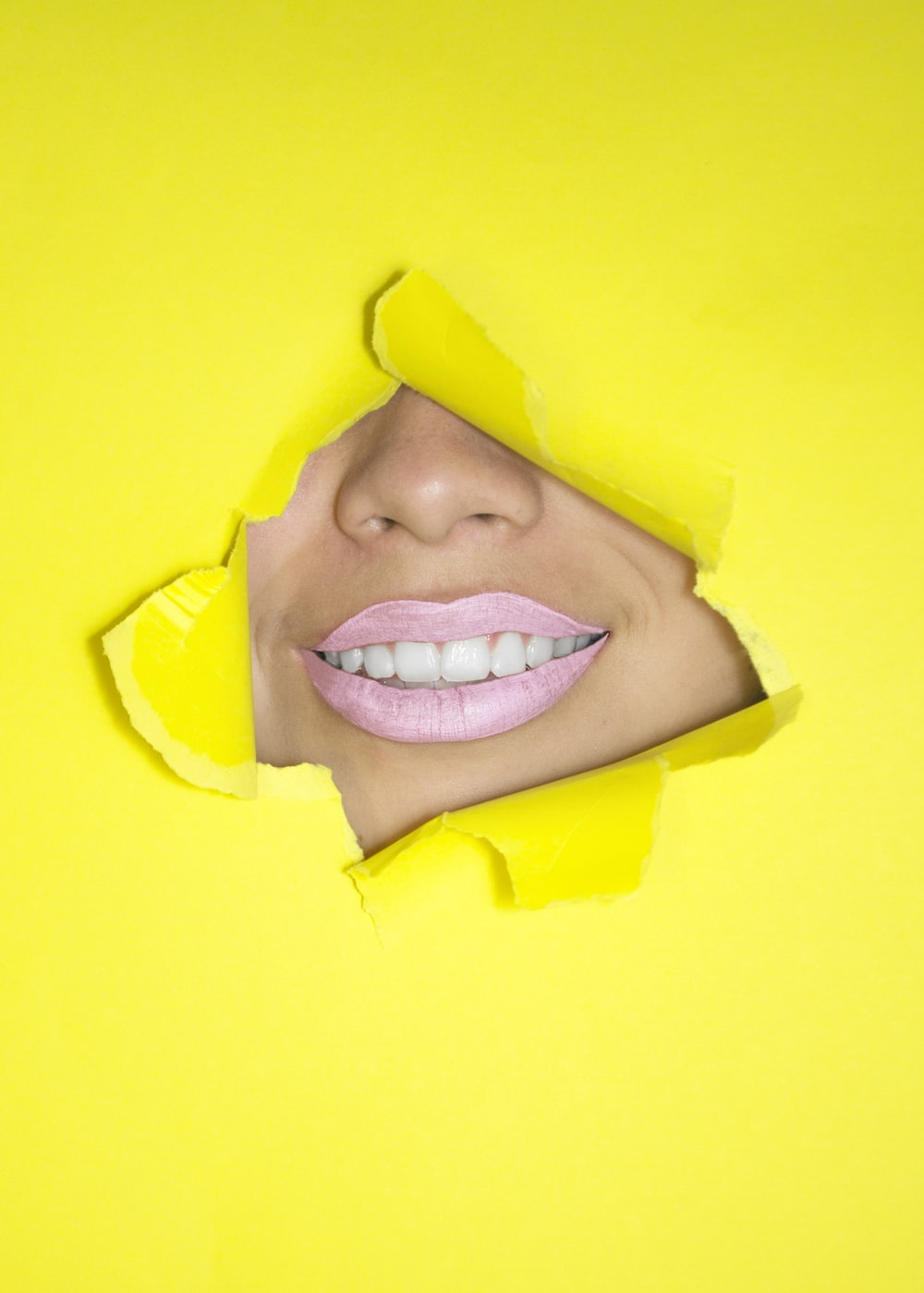 ripped yellow paper showing woman's nose and lips