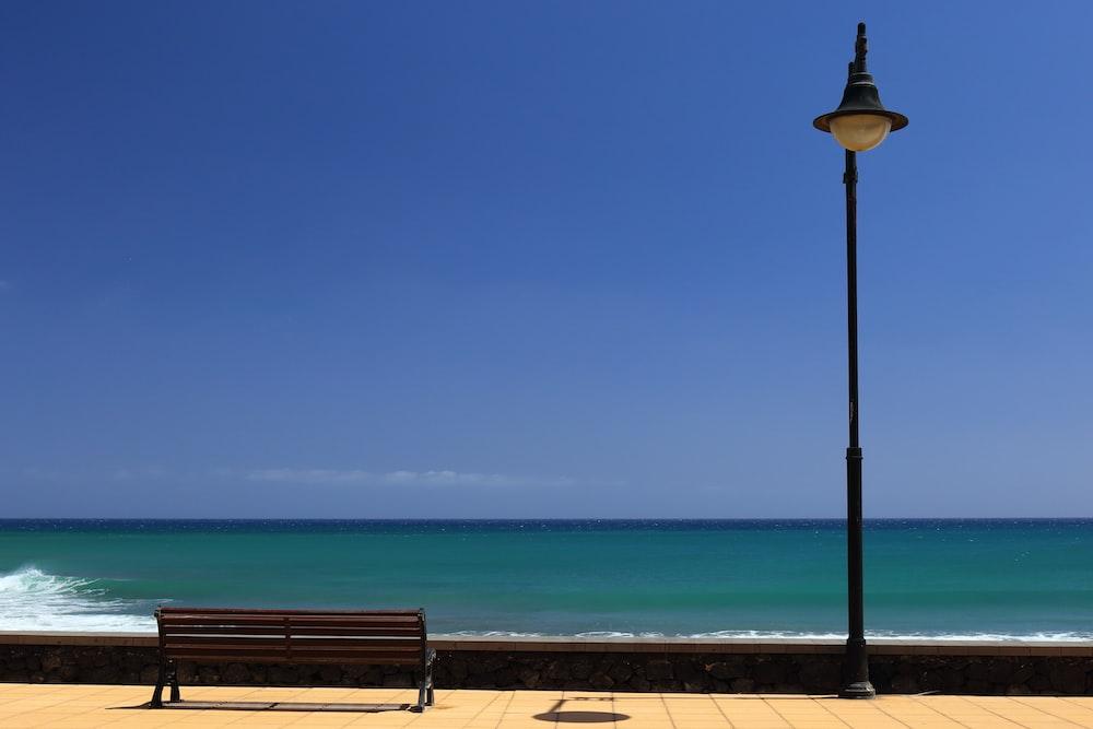 black street lamp near brown wooden waiting bench