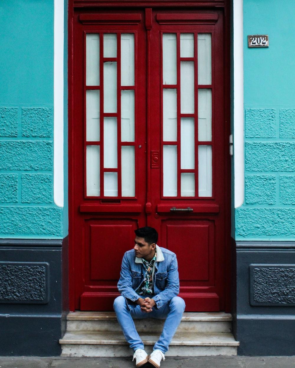 man sitting in front of door