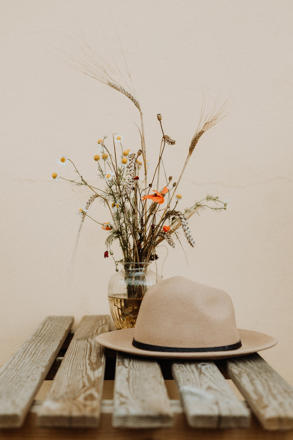 brown hat on wooden table beside flower in vase