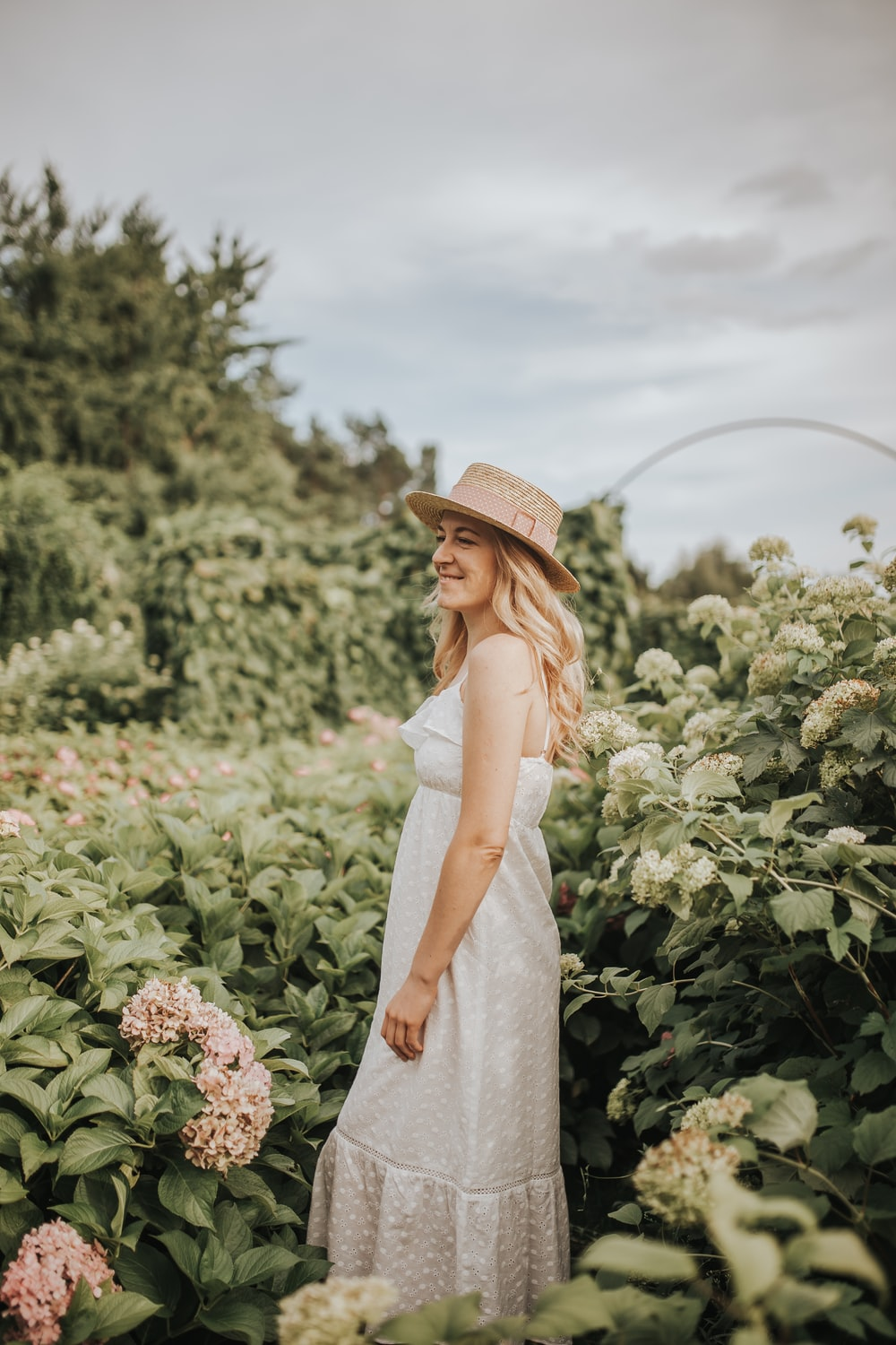woman wearing white dress and brown hat standing beside flower field