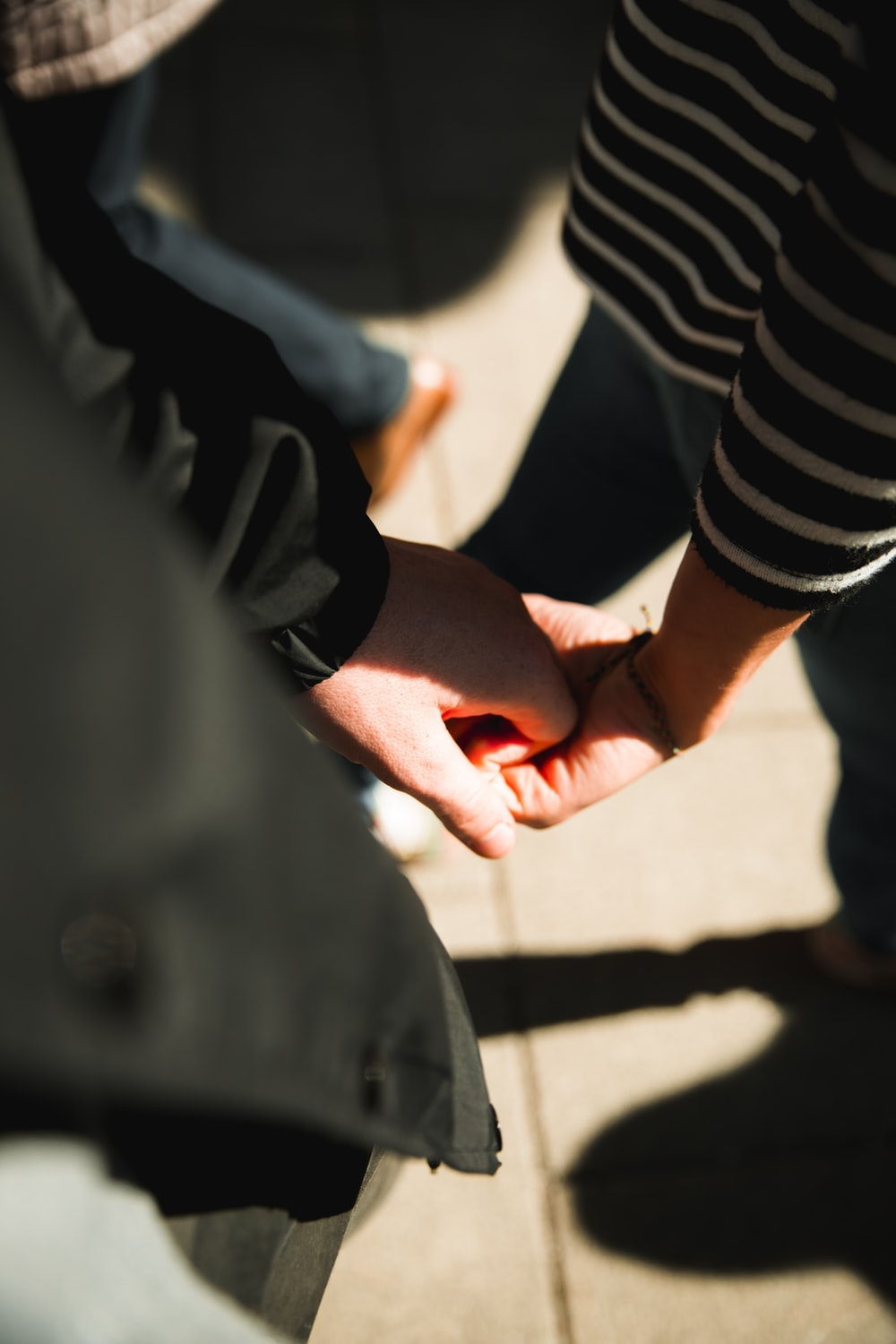 two persons holding each other hands